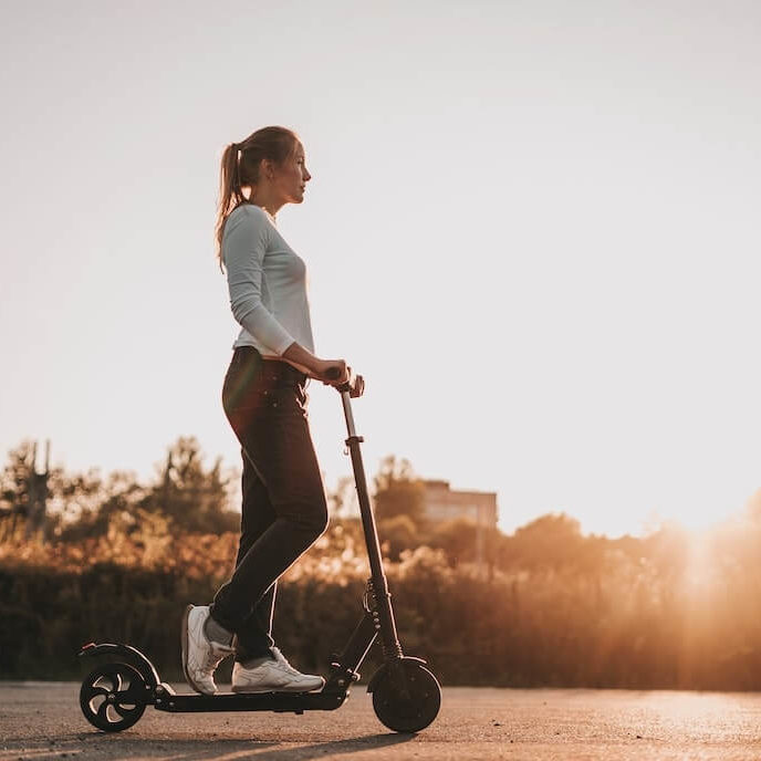 Mujer montando un patin electrico, contra la puesta de sol
