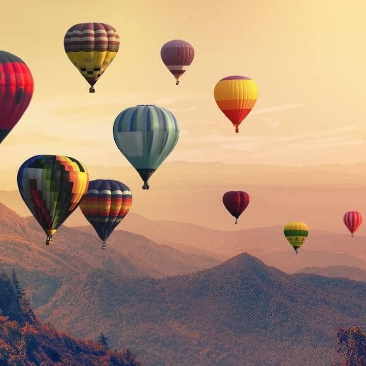 Globos aerostaticos flotando en el cielo mientras cae la tarde entre las montañas
