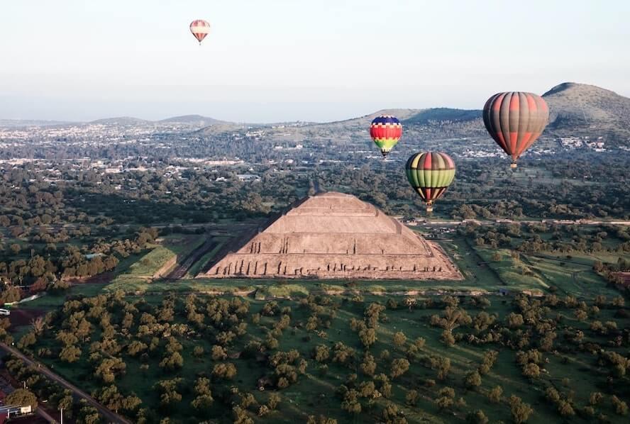 Vista aérea de la Pirámide del Sol, rodeada de globos aerostáticos durante el atardecer