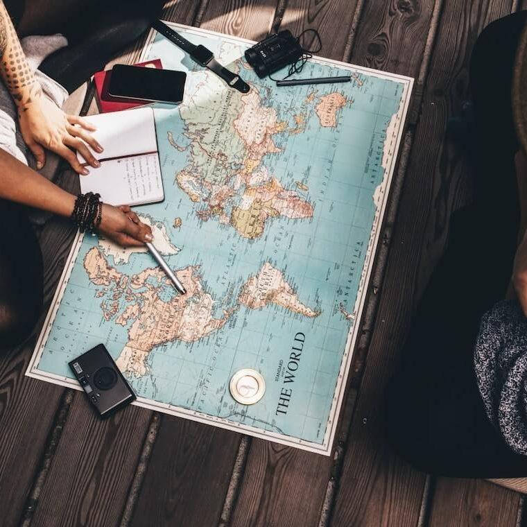 Un hombre y una mujer sentados en el piso con un mapa frente a ellos discutiendo sobre destinos locales para viajar