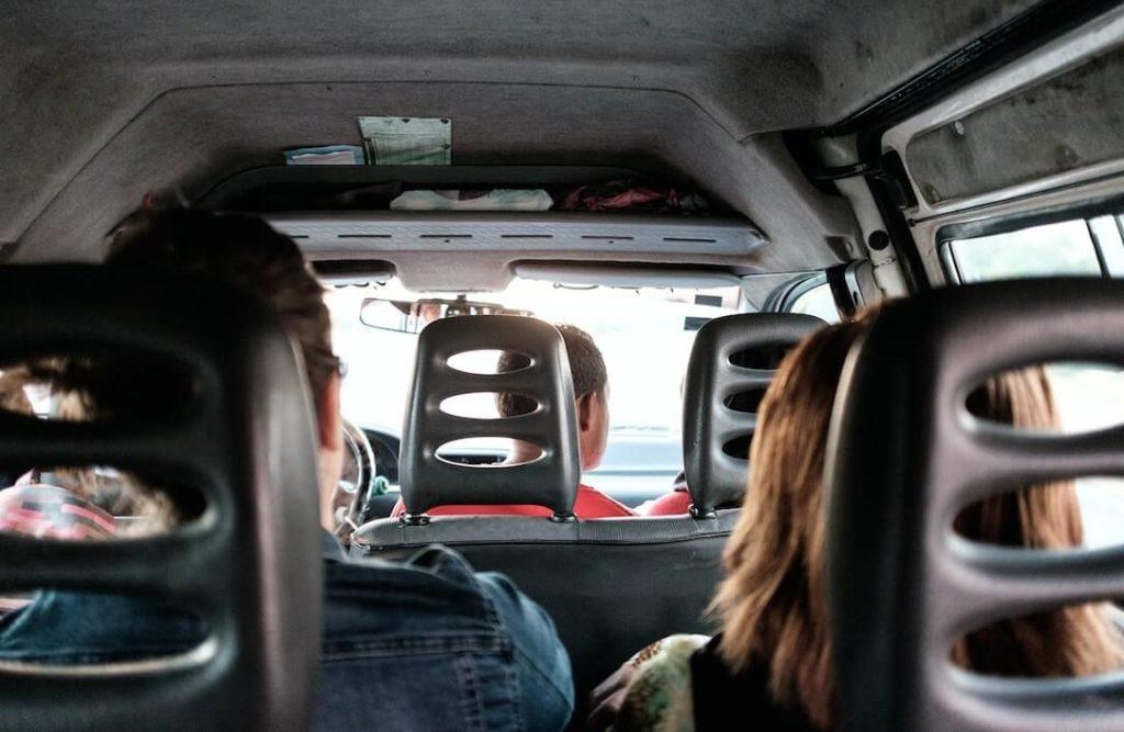 Foto de un grupo de personas compartiendo un viaje, sentadas en la parte trasera de una van