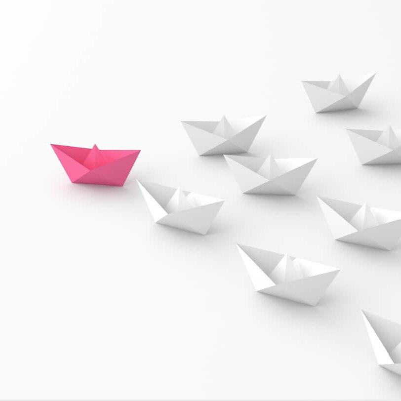 Representacion de mujeres lideres, mediante un barco rosa liderando barcos blancos