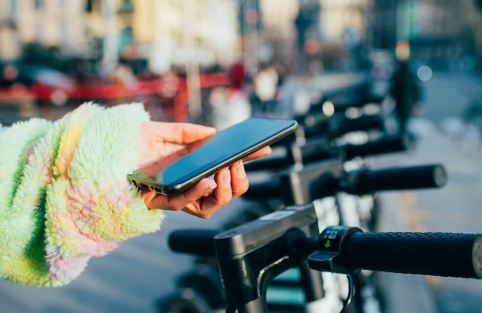Mujer usando una app de transporte para reservar un patin electrico