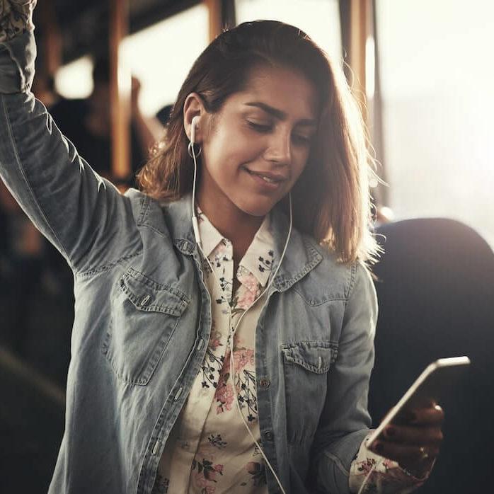 Mujer joven escuchando musica en un autobus
