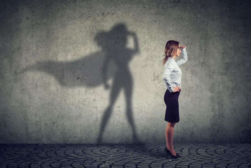 Mujer profesional y su sombra como superheroe