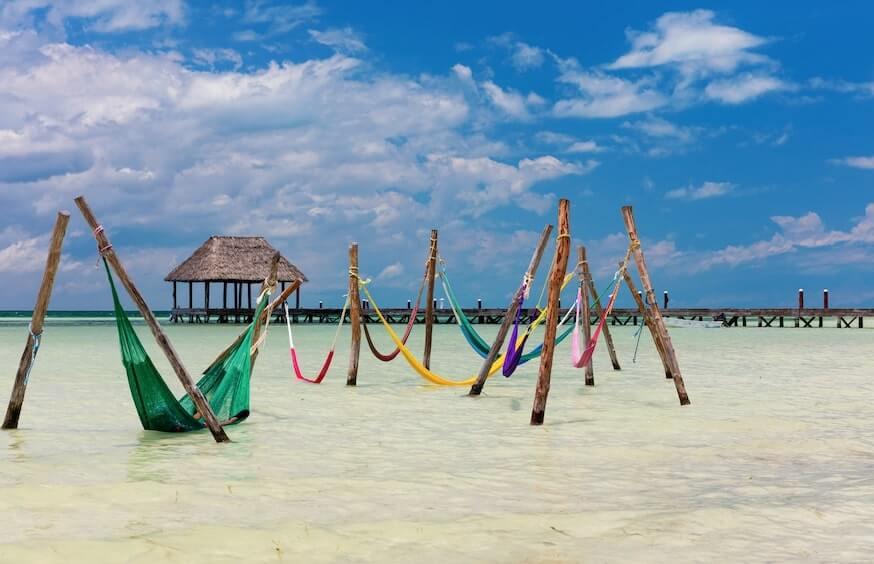 Hamacas en la playa en la Isla Holbox con una palapa de fondo