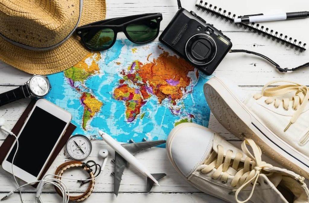 Vista de los accesorios del viajero y articulos esenciales de vacaciones como tennis, sombrero, gafas, celular y camara