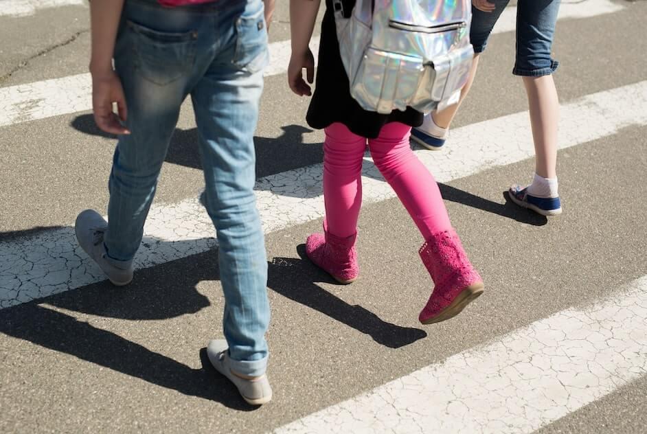 Estudiantes cruzando la calle de camino a la escuela, por un paso de peatonal, como lo indica la educacion vial