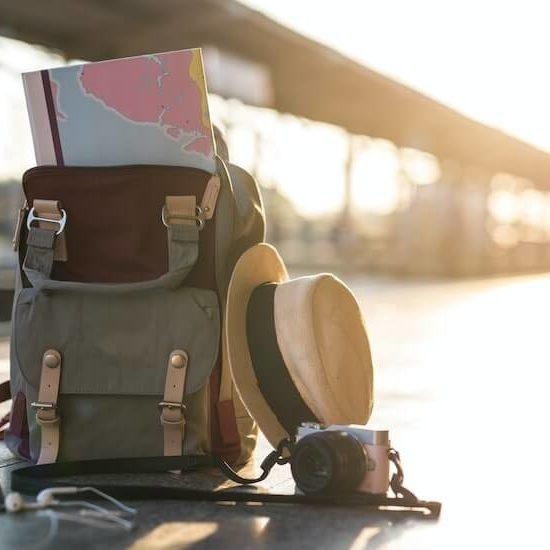 Mapa en mochila, sombrero y camara en una estacion de tren durante la puesta de sol